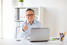 Man giving thumbs up at computer