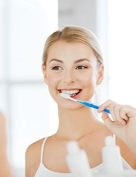 Young woman with a dental implant brushing her teeth.