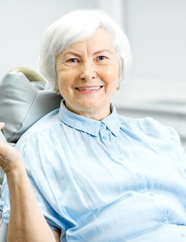 An older woman sitting in the dentist chair holding an apple