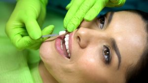 Woman having porcelain veneers attached