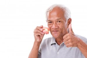 Man gives thumbs up for caring for dentures in Dallas, GA