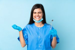 a dental assistant smiling and holding dental instruments