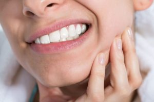 Woman with a toothache after teeth whitening